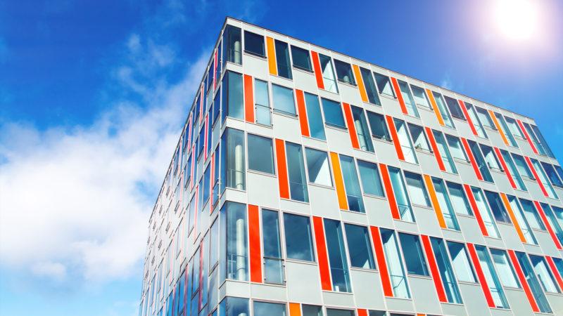 Modernes Bürogebäude mit bunter Glasfassade und spiegelnden Glasfenstern vor strahlend, blauem Himmel